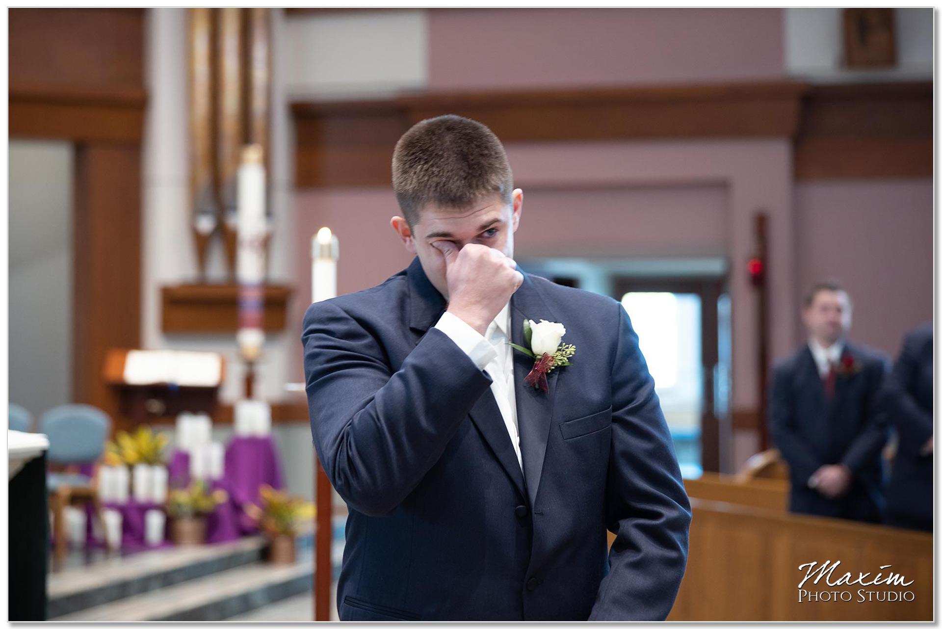 Groom looking at bride walking down aisle